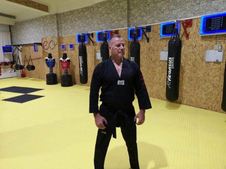 Taekwondo head master standing before MFS system