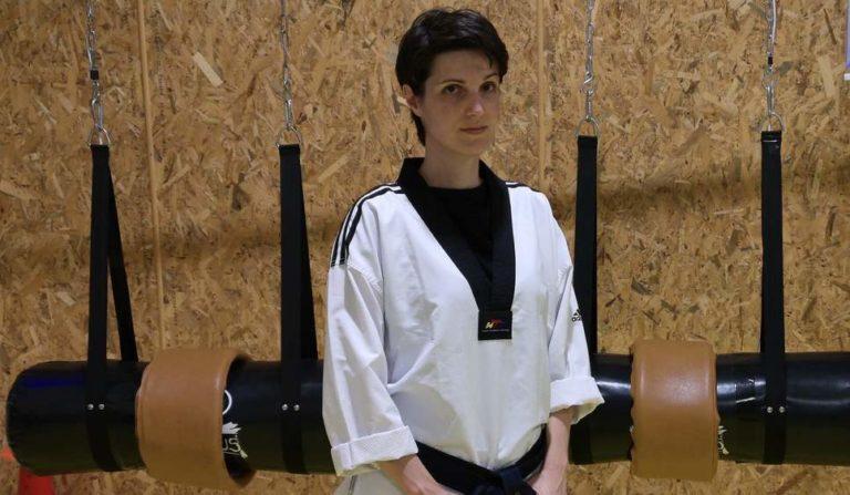 Taekwondo lady coach standing before MFS electronic system