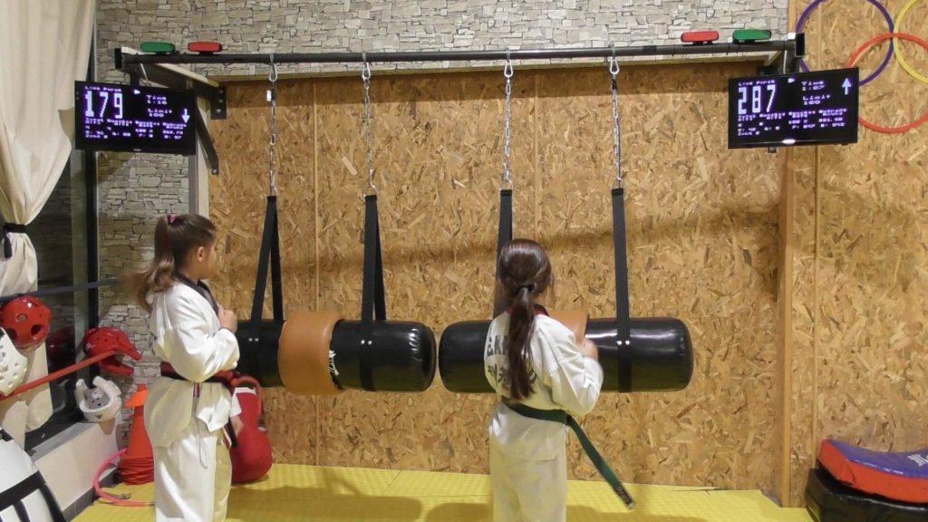 Taekwondo girls kicking horizontal MFS bags